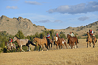 USA, Wyoming, cowboys and cowgirls herding horses in wilderness - RUEF001382