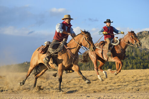USA, Wyoming, two riding cowboys - RUEF001389