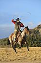 USA, Wyoming, riding cowboy swinging lasso - RUEF001390