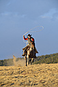 USA, Wyoming, riding cowboy swinging lasso - RUEF001392