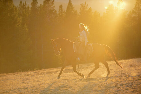 USA, Wyoming, riding cowgirl at backlight - RUEF001400