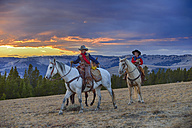 USA, Wyoming, two young cowboys riding in wilderness at sunset - RUEF001414