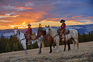 USA, Wyoming, two young cowboys sitting on their horses at sunset - RUEF001419