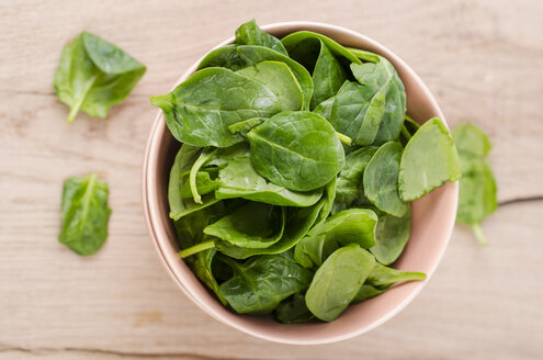 Bowl of fresh spinach leaves on wood - ODF001010