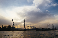 Germany, Hamburg, harbour cranes at Elbe river in the evening - KRPF001217