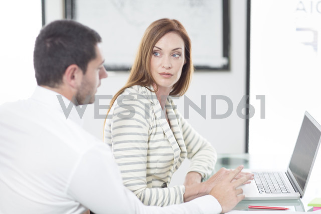 Businesswoman and businessman in office working on laptop - ZEF003097