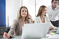 Businesswomen and businessman in office working on laptops - ZEF003100