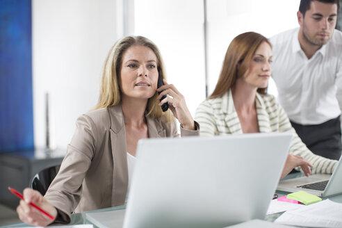 Businesswomen and businessman in office working on laptops - ZEF003100