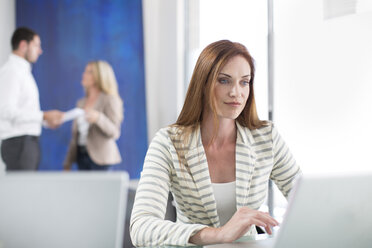 Businesswoman in office working on laptop - ZEF003106