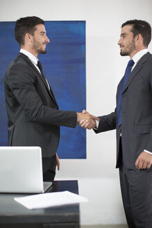 Two businessmen shaking hands in office - ZEF003112