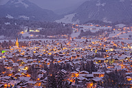 Germany, Bavaria, view to snow-covered lighted Oberstdorf at twilight in front of the Allgaeu Alps - WG000560