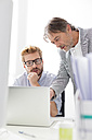 Two businessmen with laptop at desk - WESTF020488