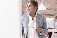 Businessman holding cup of coffee in office - WESTF020523