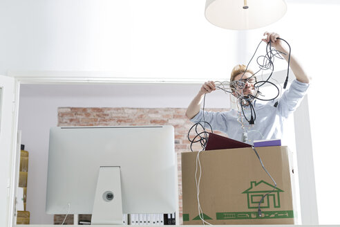 Young man with cable tangle in office - WESTF020547