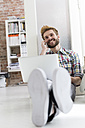 Young man sitting on floor in office using laptop and cell phone - WESTF020562