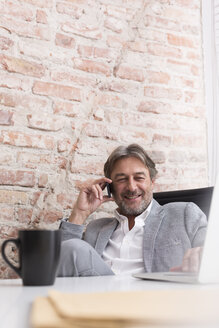 Smiling businessman on cell phone at desk - WESTF020632