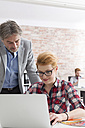 Businessman and woman with laptop in office - WESTF020656