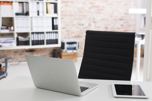 Laptop and digital tablet on desk in office - WESTF020659