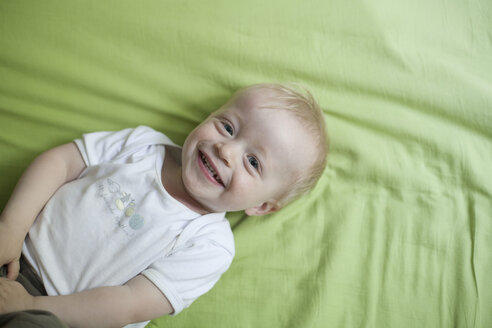Portrait of smiling little boy lying on bed - RB002240