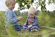 Two little brothers sitting on a meadow - RB002255