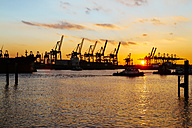 Germany, Hamburg, harbour, cranes at Elbe river at sunset - KRPF001277