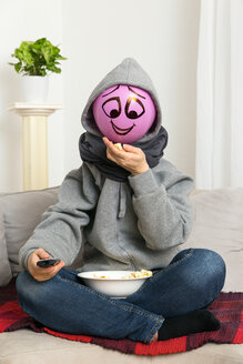 Balloon person with remote control sitting on couch eating popcorn - MIDF000024