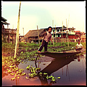 boy steering longtail boat through floating village, inle lake, myanmar - LUL000213