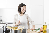 Portrait of smiling young woman cooking - FLF000806