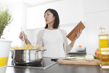 Young woman holding digital tablet while cooking spaghetti - FLF000810