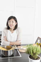 Portrait of smiling young woman cooking spaghetti - FLF000813