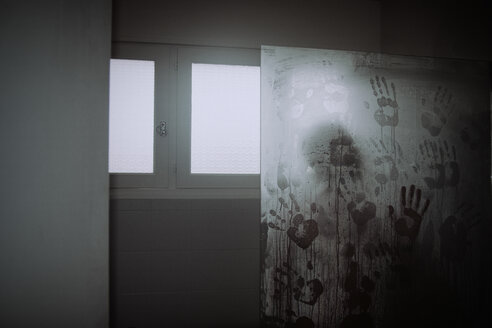 Man in shower with hand prints on glass pane - ON000771