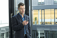Businessman using smartphone in an office - SHKF000136