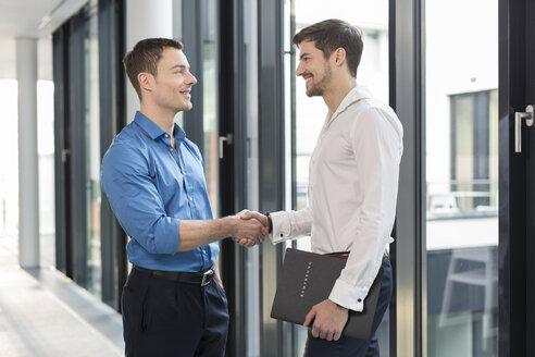 Two Businessmen shaking hands in an office - SHKF000137