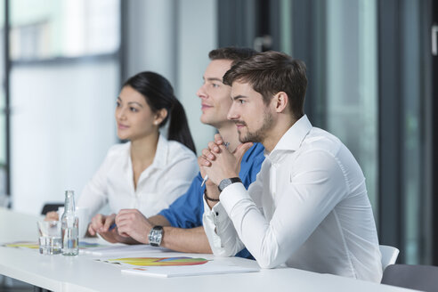 Three business people listening in a conference room - SHKF000147