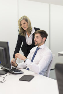 Businesswoman and businessman at desk looking at computer monitor - SHKF000174