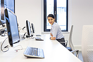 Portrait of smiling woman at desk in office - SHKF000195