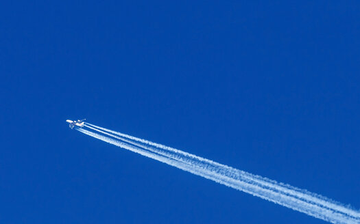 Flying airplane and vapour trail in front of blue sky - EJWF000637