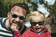 Portrait of father and daughter with exchanged sunglasses - IP000179