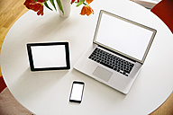 Three mobile devices on a white round table with red tulips - MFF001390