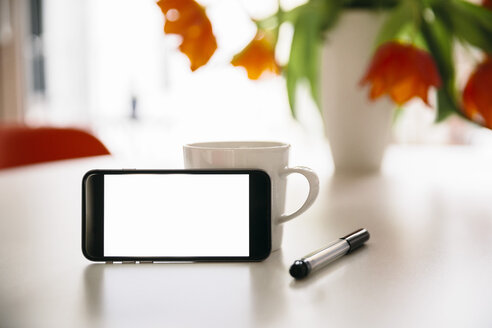 Smart phone leaning at a coffee cup on a white round table with red tulips - MFF001394