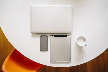 Three mobile devices and coffee on a white round table - MFF001387