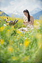 Young woman having picnic on alpine meadow - HHF005032