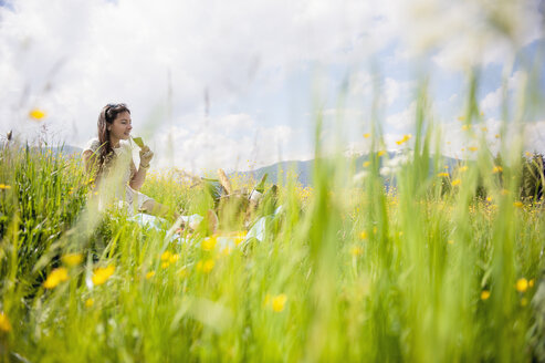 Young woman having picnic on alpine meadow - HHF005042