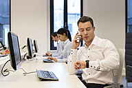 Man at desk on cell phone with colleagues in background - SHKF000198