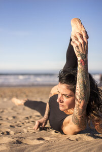 Spain, Asturias, Aviles, woman practicing yoga on the beach - MGOF000026