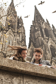 Germany, Cologne, young couple watching city map in front of Cologne Cathedral - FEXF000237