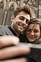Germany, Cologne, young couple taking selfie in front of Cologne Cathedral - FEXF000240