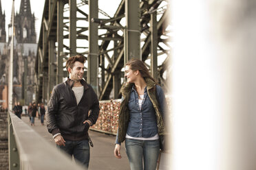 Germany, Cologne, young couple walking on Hohenzollern Bridge - FEXF000252