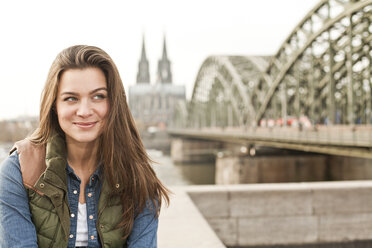 Germany, Cologne, portrait of smiling young woman - FEXF000255