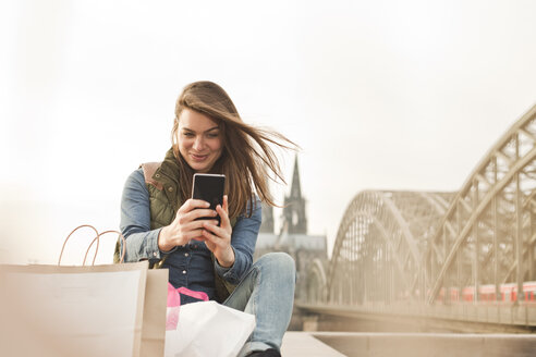Germany, Cologne, smiling young woman with shopping bags taking a selfie - FEXF000258
